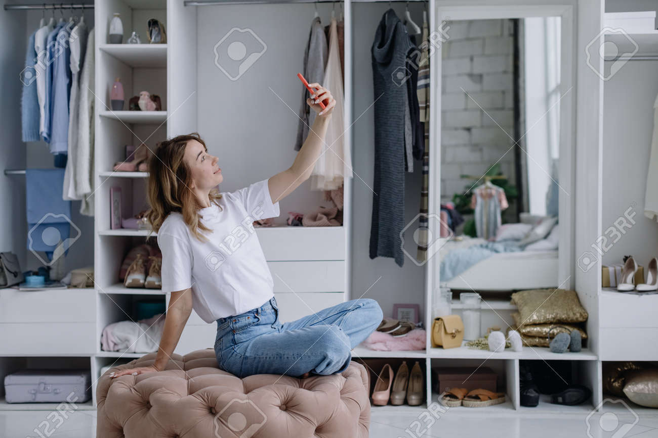 Young woman sits in a modern dressing room with a phone taking a selfie - 166079673