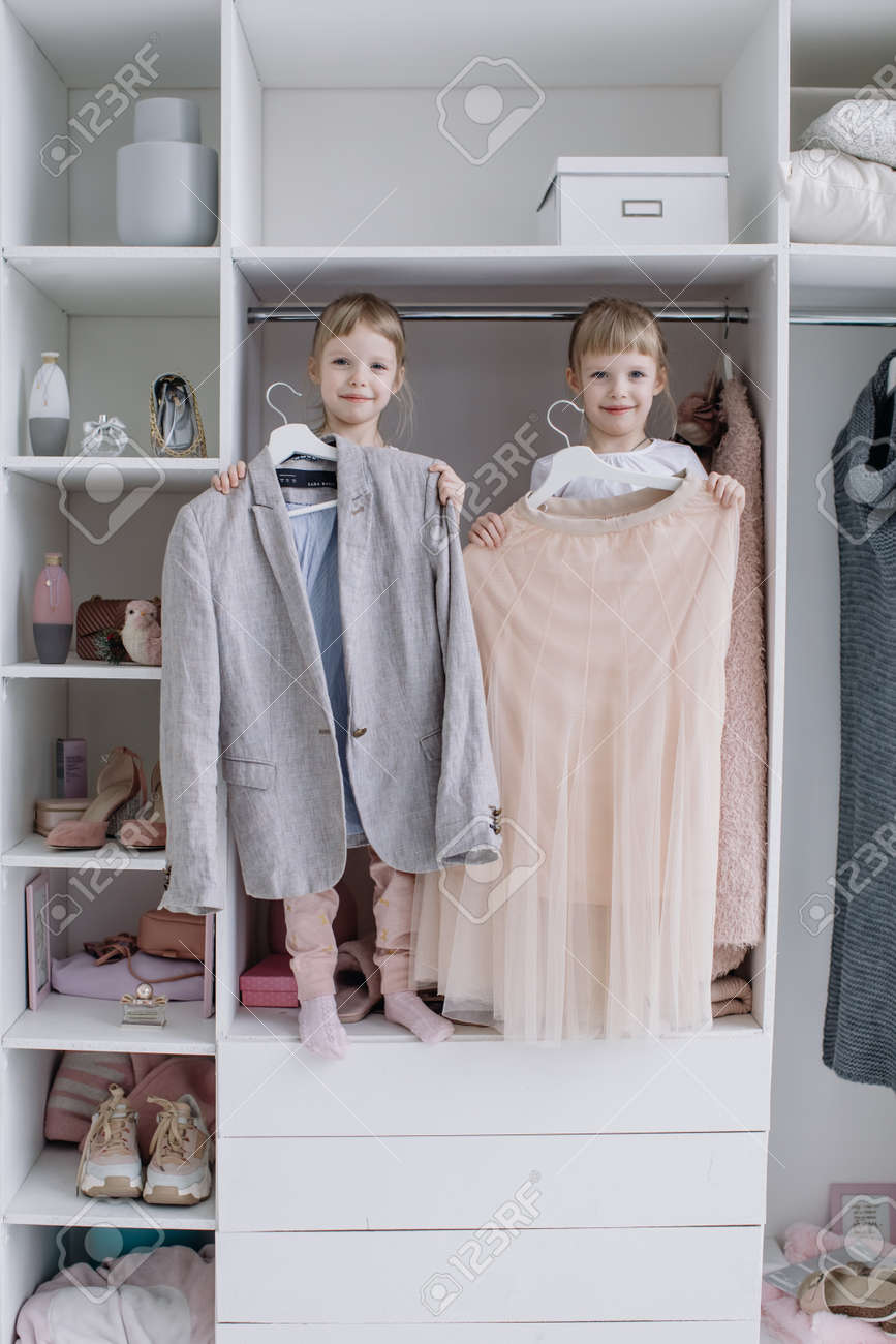 Family wardrobe. Happy twin sisters on shelve in closet with natural organic clothes in cozy dressing room play joyfully - 166079667