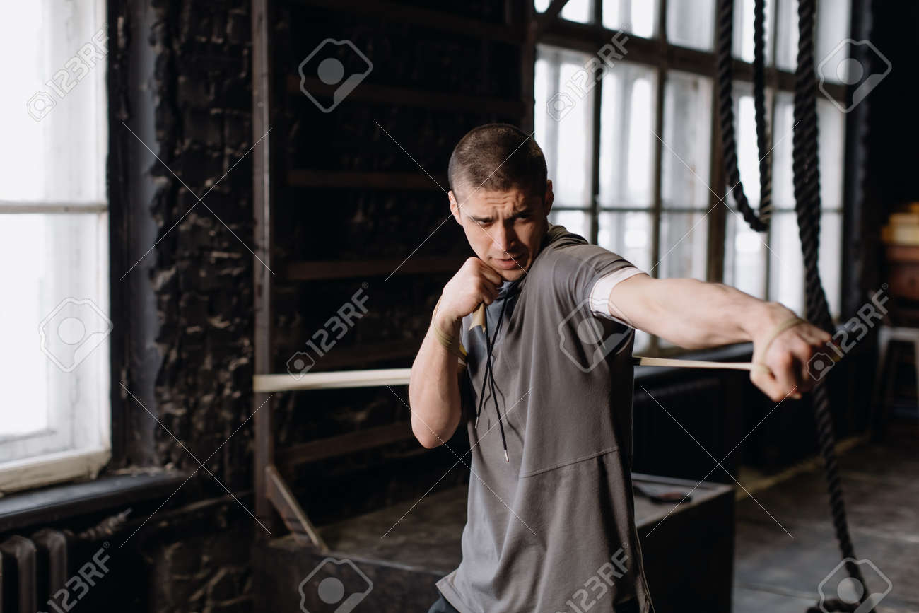 Cool man fighter in boxing bandages trains in the gym. Mixed martial arts - 166083842
