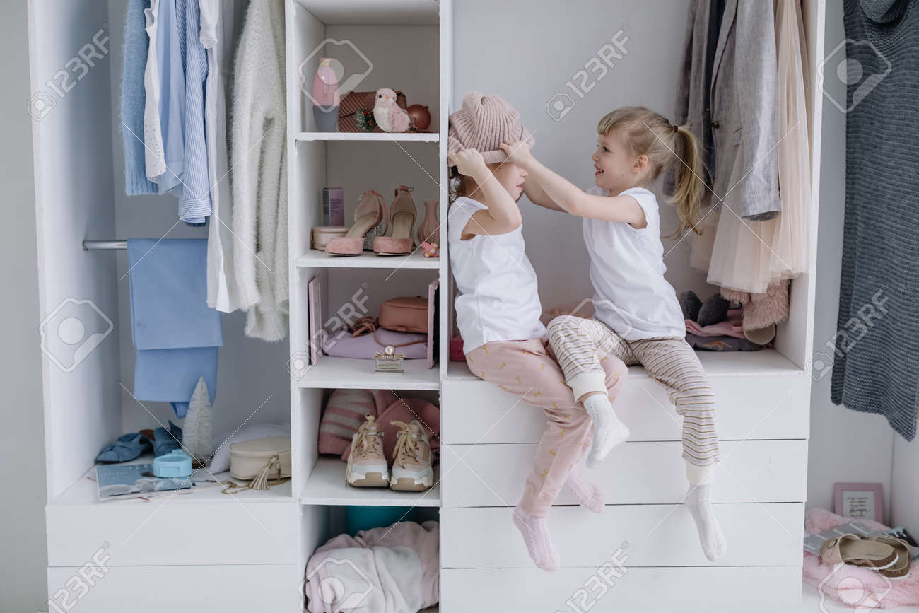 Family wardrobe. Happy twin sisters on shelve in closet with natural organic clothes in cozy dressing room play joyfully - 166083843