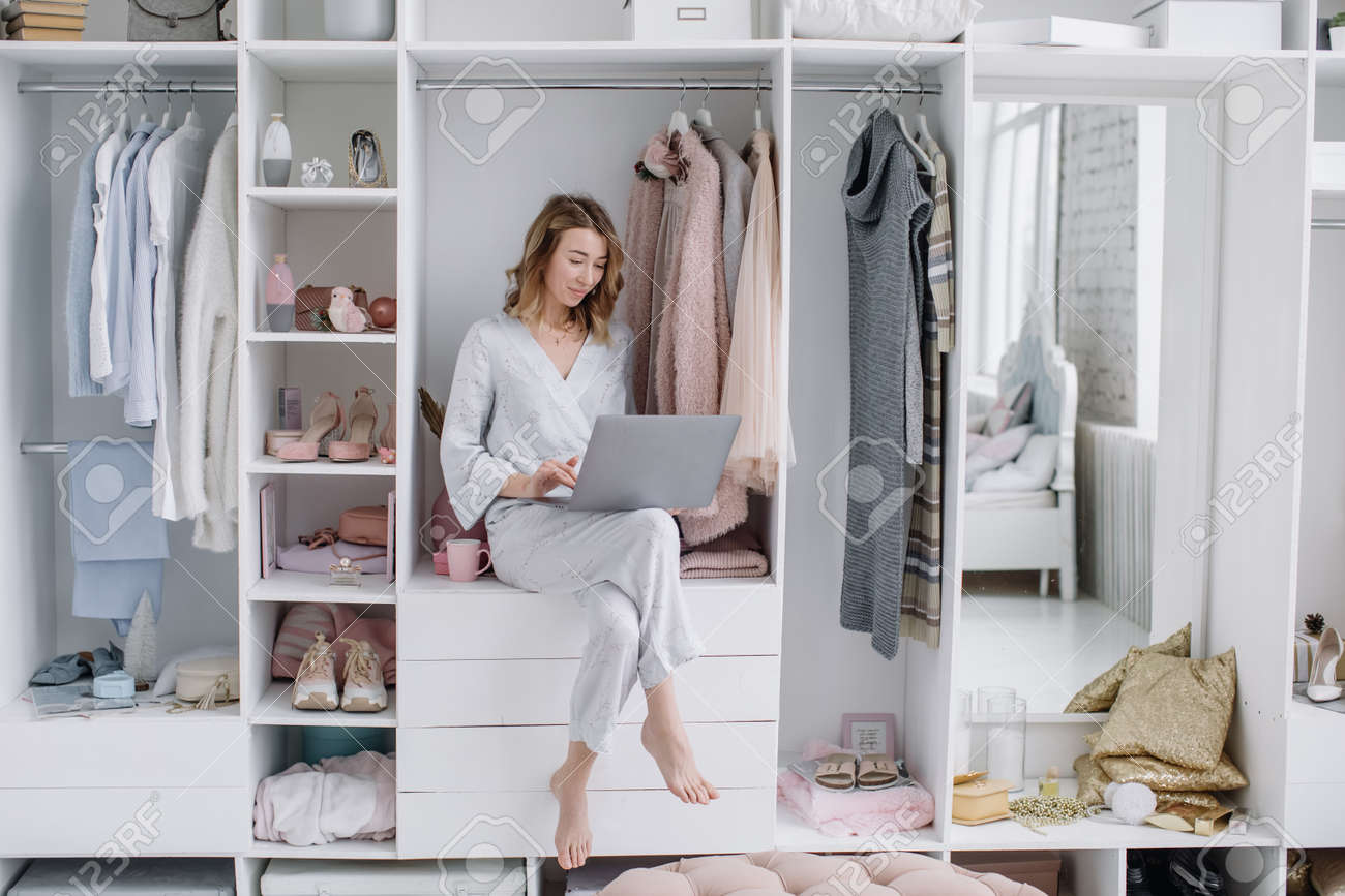 Young woman chooses things online from the comfort of your dressing room. Online shopping - 166079981