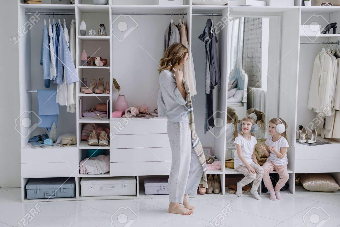 Young woman chooses a dress in her modern dressing room. Mom shows her daughters a dress - 166080087