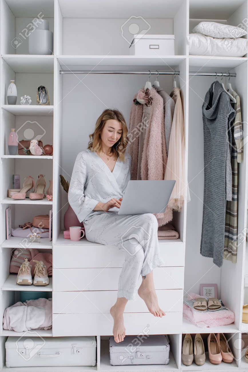Young woman chooses things online from the comfort of your dressing room. Online shopping - 166080181