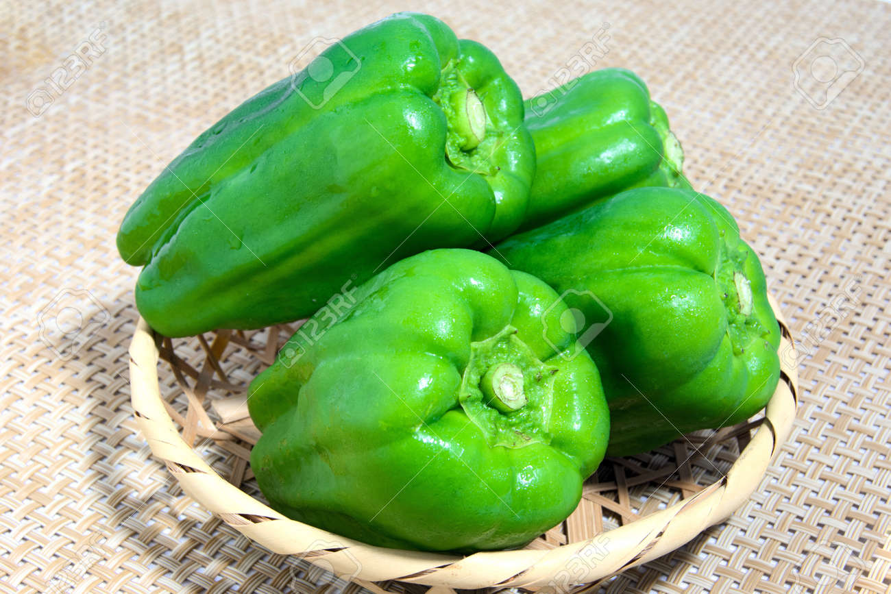 Green pepper went into a bamboo basket - 60387326
