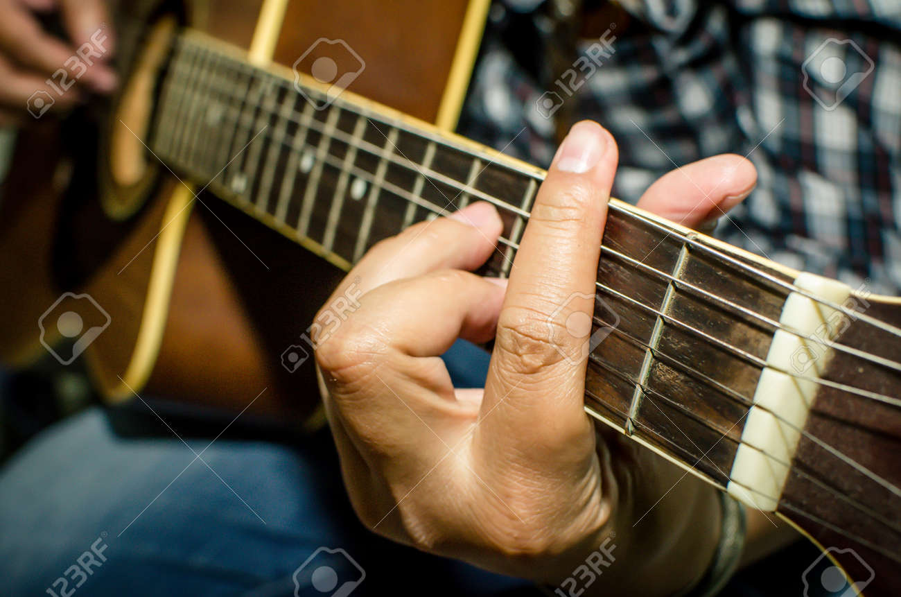 Acoustic Guitar Being Played Fingers Holding A Chord Stock Photo