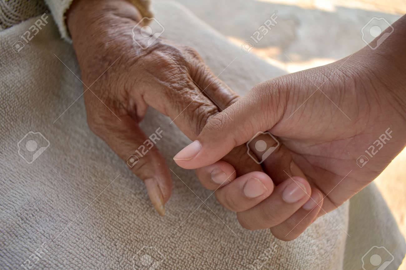 Close up granddaughter takes care of the health sick grandmother at home by holding hands. Lifestyle support the love of the family. - 148586722