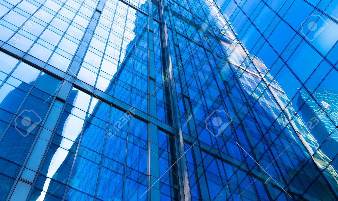 Reflection on glass facades of modern skyscraper in sunny day. Concept of business background with architecture details of financial district building - 122531567