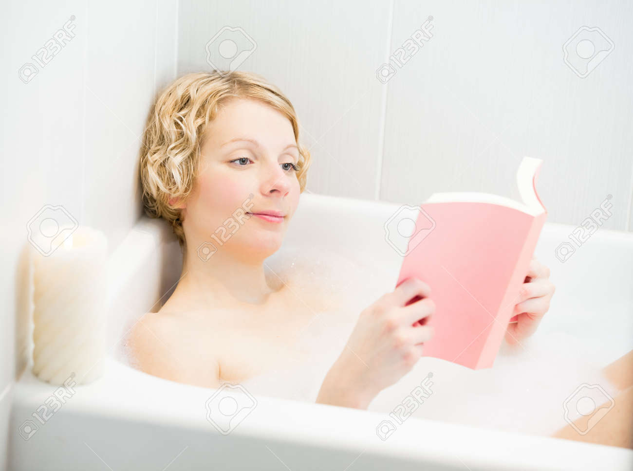 Young Woman Relaxing And Reading A Book In The Bath With Candlelight ...