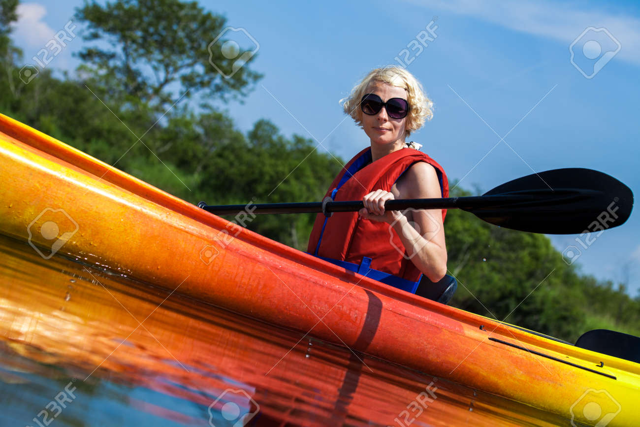 1e38d7fa56 Stock Photo - Young Woman Kayaking Alone on a Calm River and Wearing a  Safety Vest