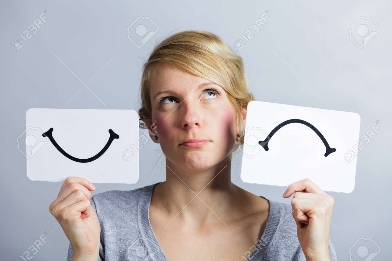 Portrait of a Questioning Woman Holding Happy and Unhappy Survey Mood Board - 38429314