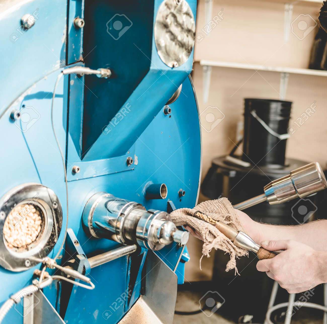 Crop shot of employee taking sample of coffee beans out of roaster