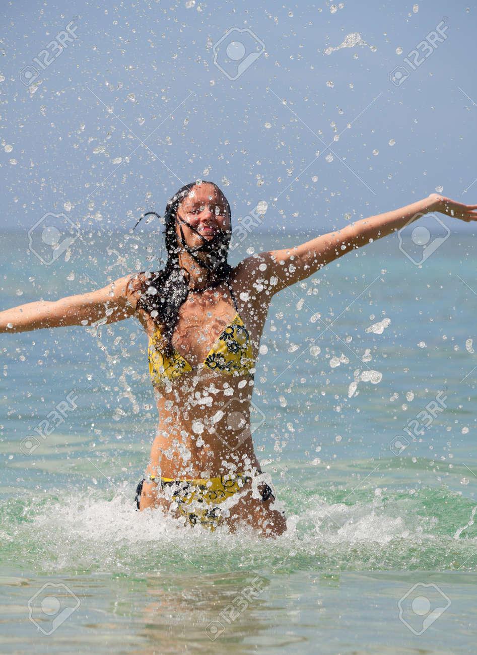 Beautiful girl and a lot of splashing sea Stock Photo - 15983935