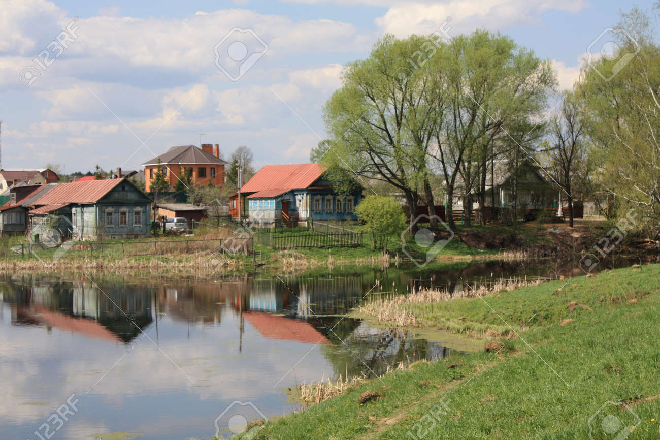Landscape Houses landscape with wooden village houses near lake, trees, reflection