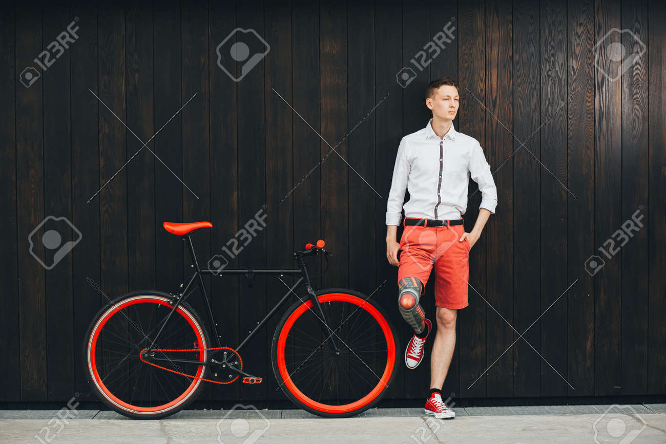 Hipster with bycicle and tatoo at dark background. Standard-Bild - 92048474