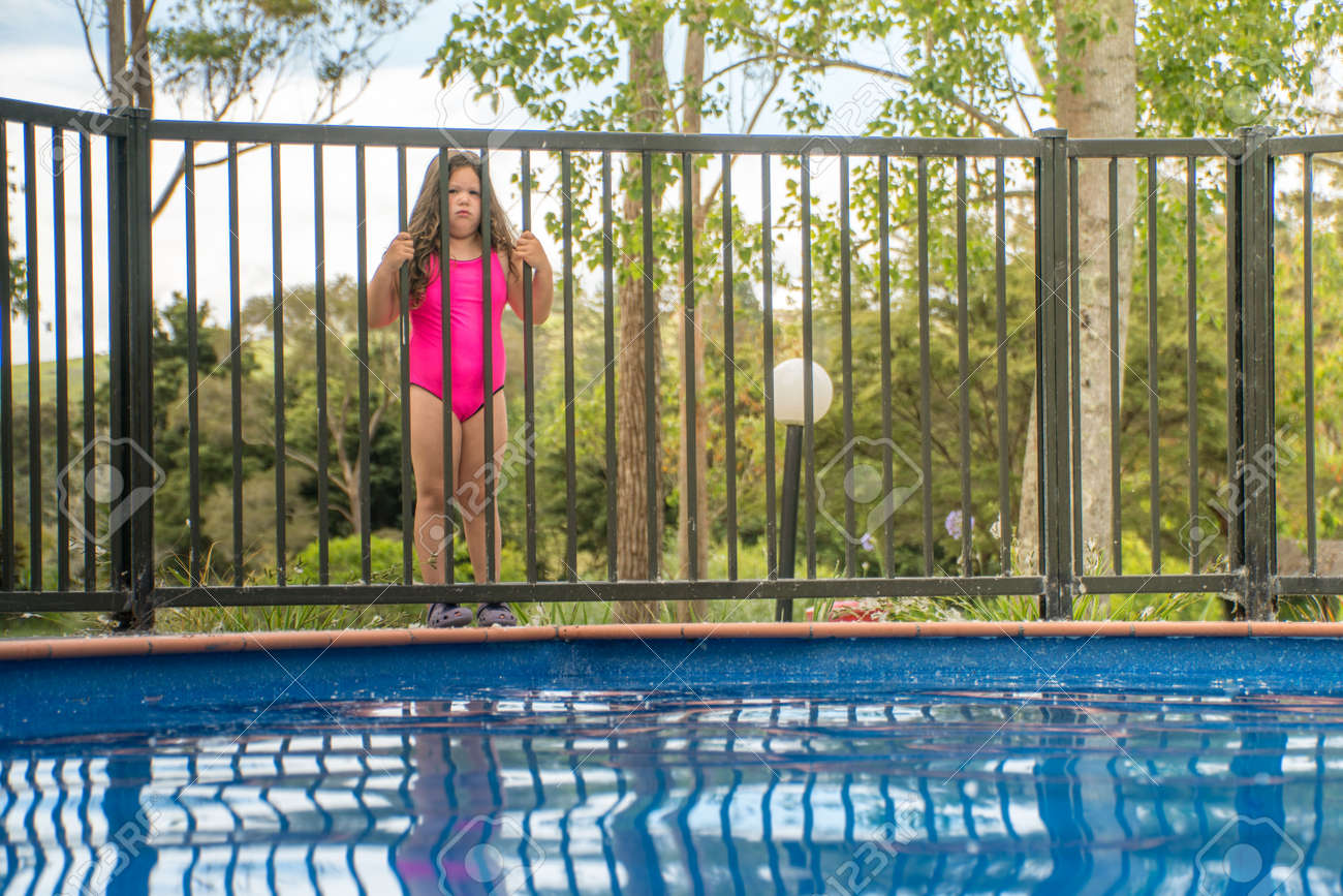 Pool Safety Young Girl Standing Outside Pool Fence Looking Stock