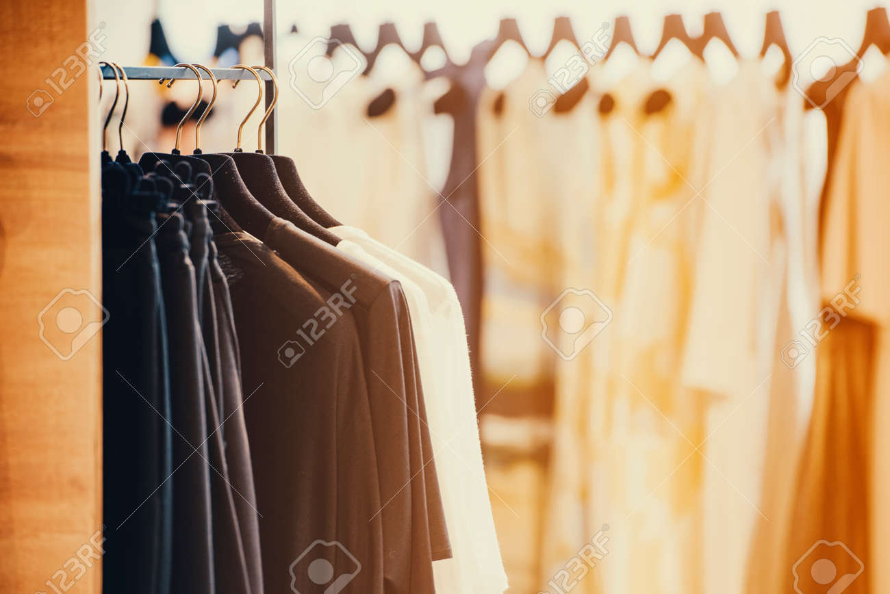 Colorful clothes on hangers in a luxury fashion store with backlight effect. - 71583423