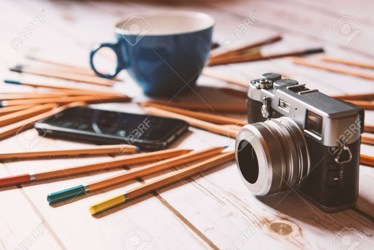 Creative workplace concept: Coffee, smart phone and camera on a wood background. Foto de archivo - 79191653