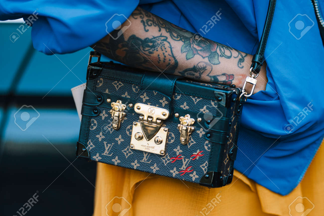 Milan, Italy - September 22, 2017: Tatoo girl with a stylish outfit wearing a Louis Vouitton luxuty handbag. - 96810447