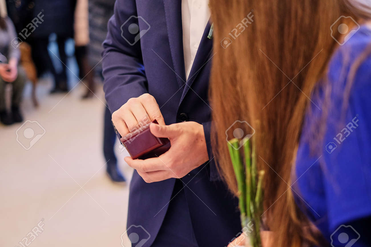 A Man In A Blue Suit Holds A Small Wooden Gift Box Of Wedding