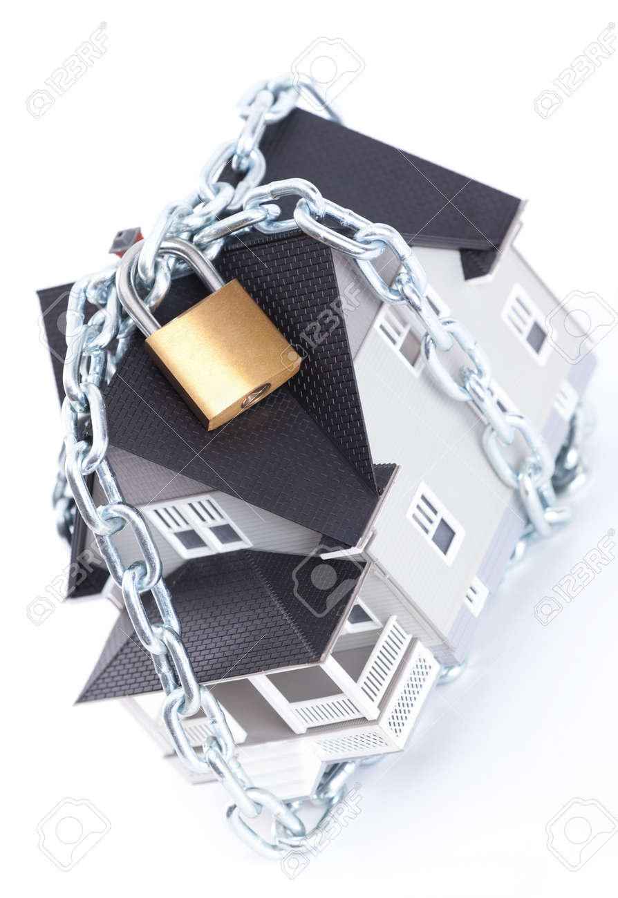 Real estate concept - chain with lock around the household architectural model, isolated Stock Photo - 13900989