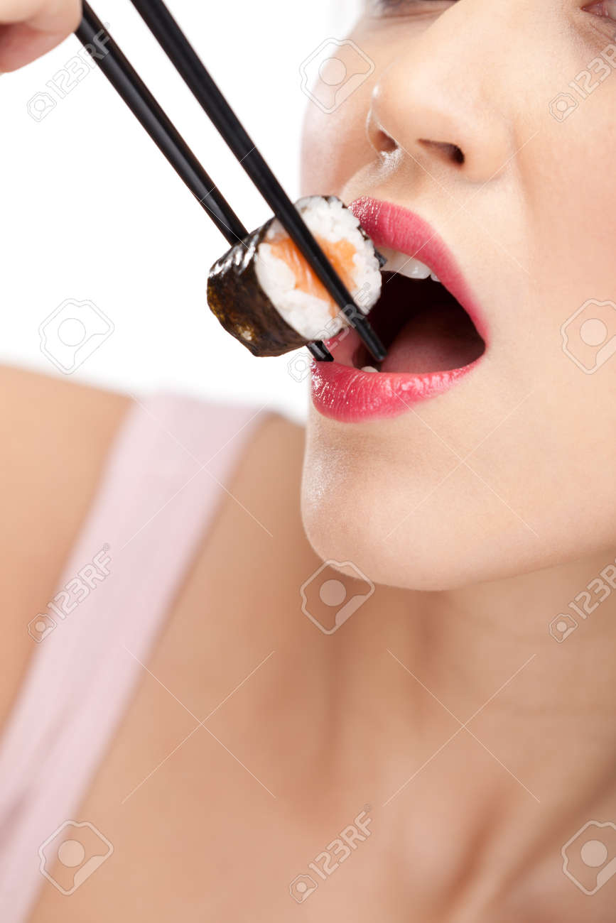 Young woman holding sushi with a chopsticks, closeup, isolated Stock Photo - 13894552