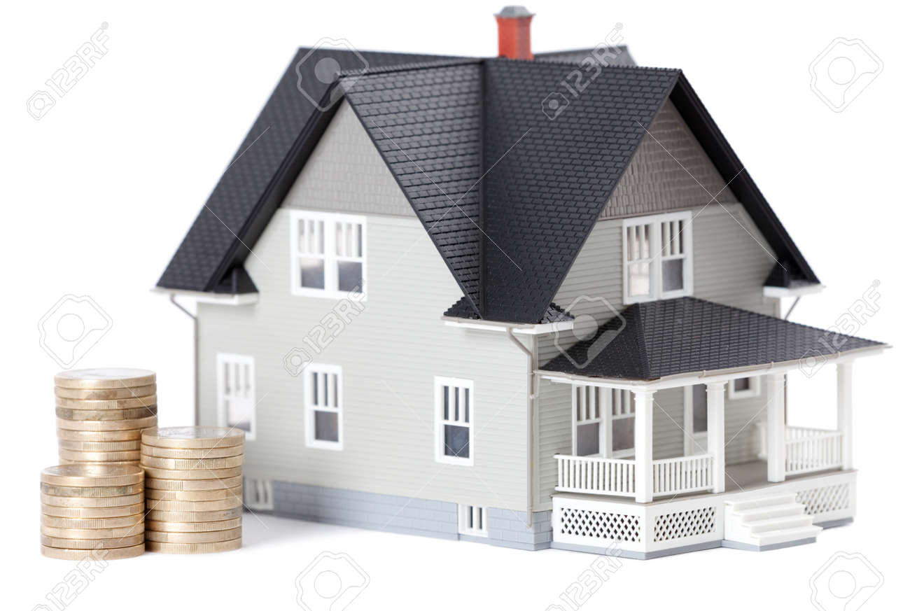 Real estate concept - stacks of coins in front of home architectural model, isolated Stock Photo - 13999826