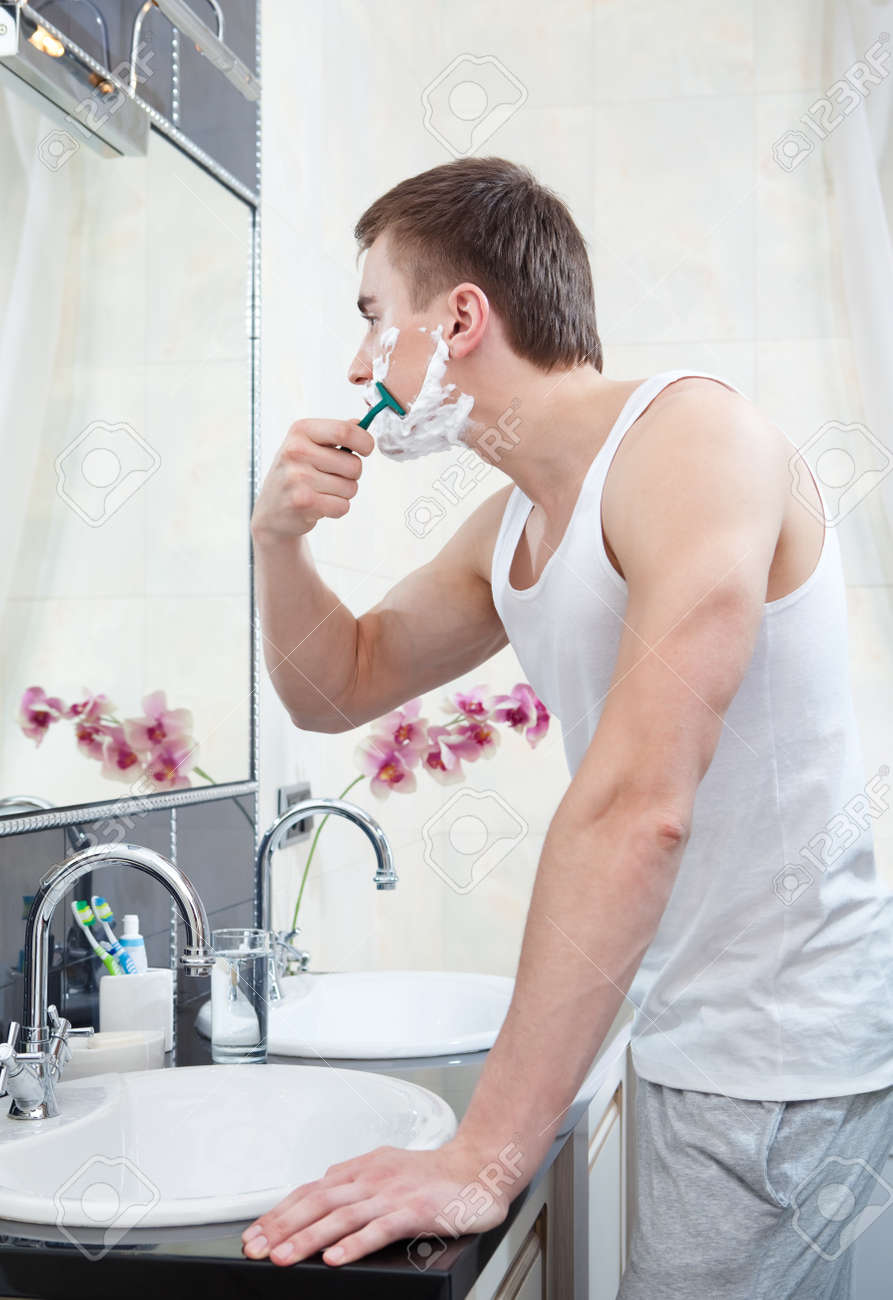 Muscular man shaves in the bathroom Stock Photo - 14980373