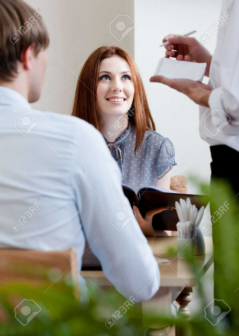 Pair makes the order to the waiter at the cafe Stock Photo - 15044387