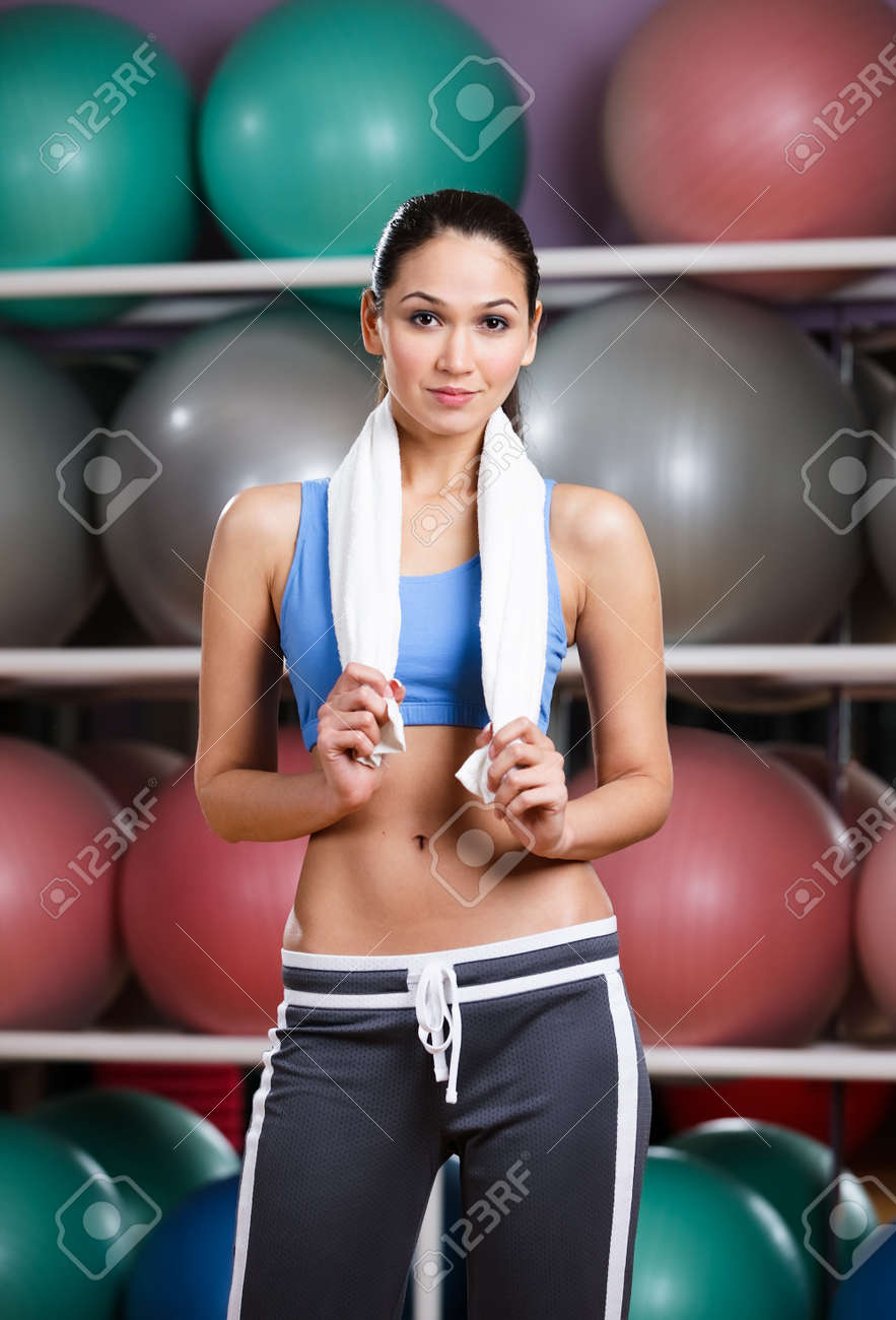 Athletic woman with perfect figure in fitness gym with shelves of gym balls Stock Photo - 15177350