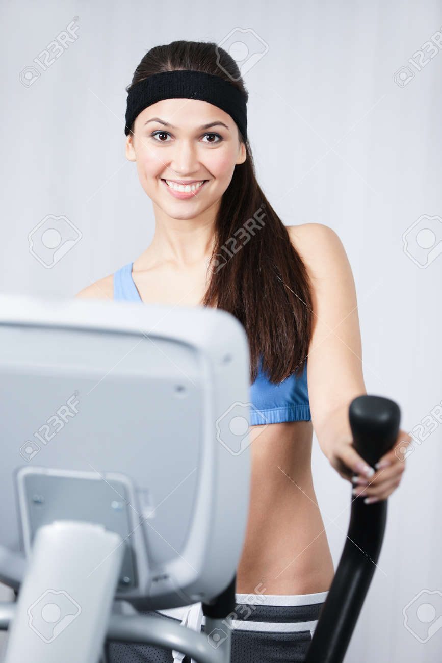 Young sportswoman training on simulators in gym Stock Photo - 15177355