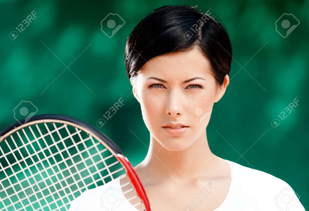 Portrait of successful female tennis player with racket at the tennis court Stock Photo - 15316316