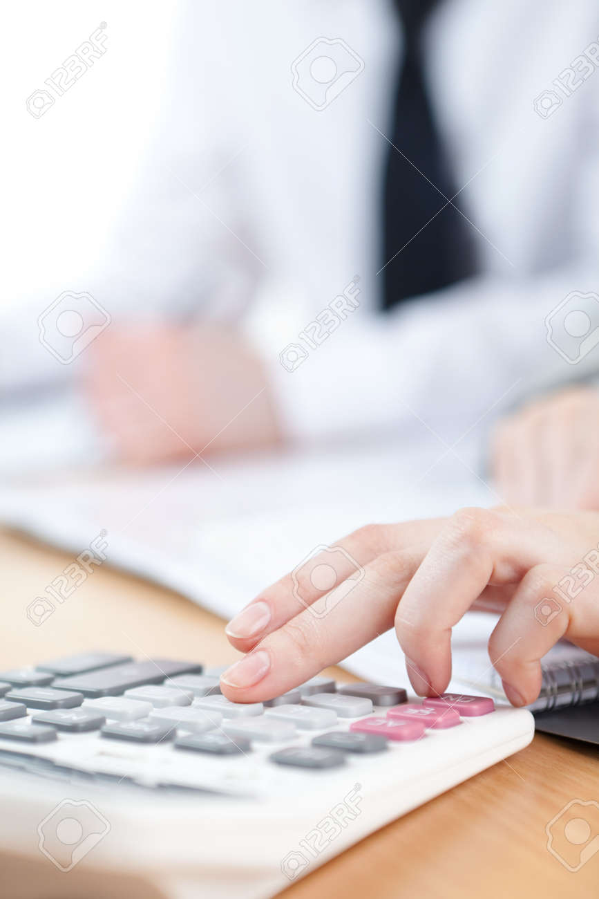 Manager counting on calculator sitting at the table. Close up of hands and stationery Stock Photo - 15541613