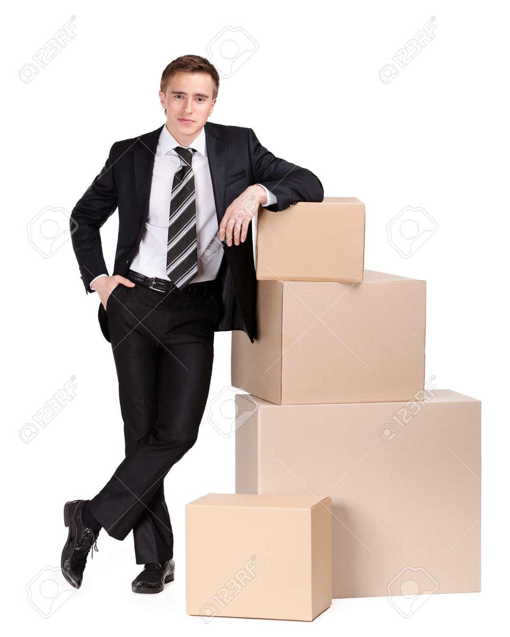 Manager in pak staat in de buurt stapel van dozen, geïsoleerd op wit