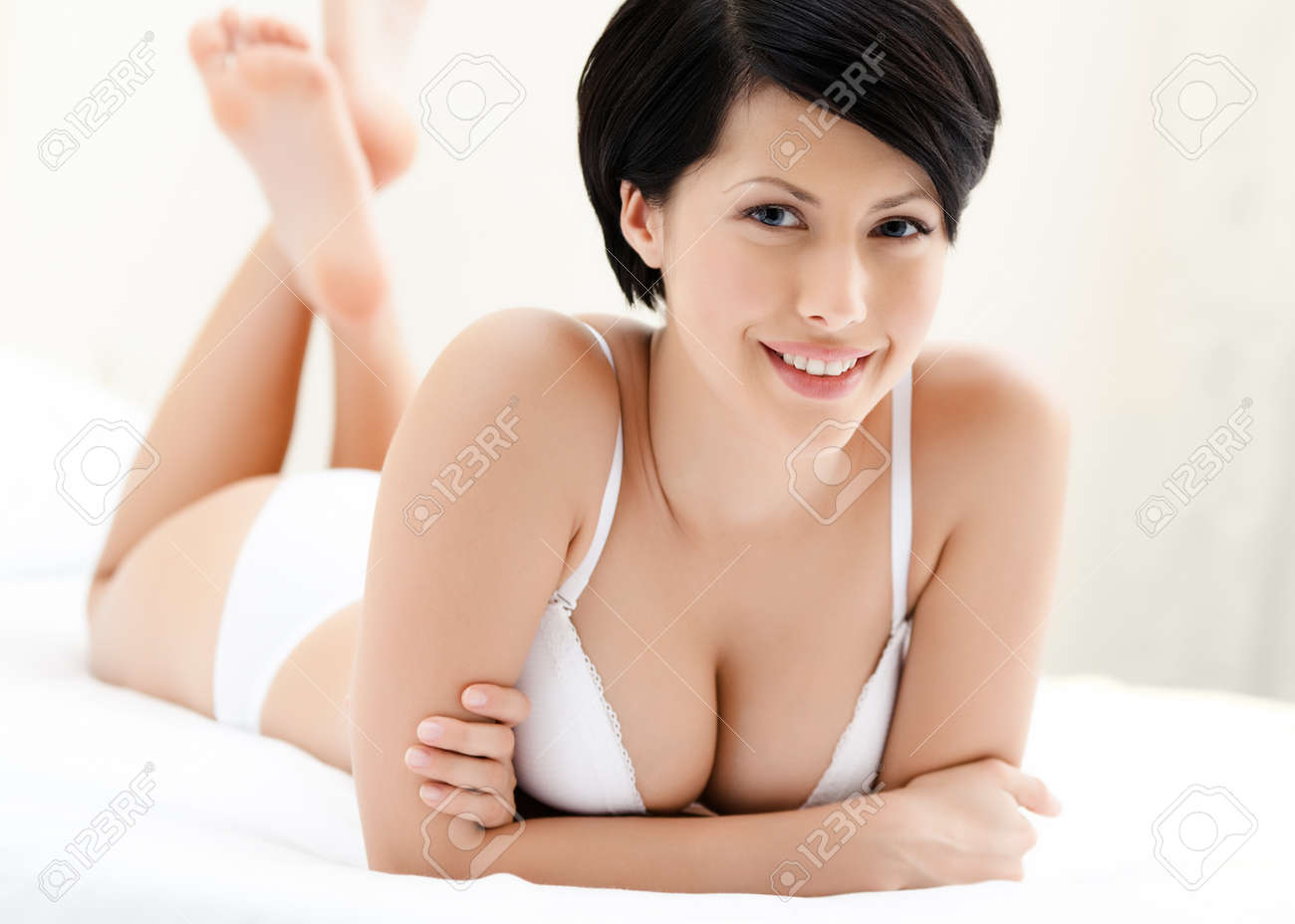 Woman in underwear is lying in the bed with white bed linen, white background Stock Photo - 15647698