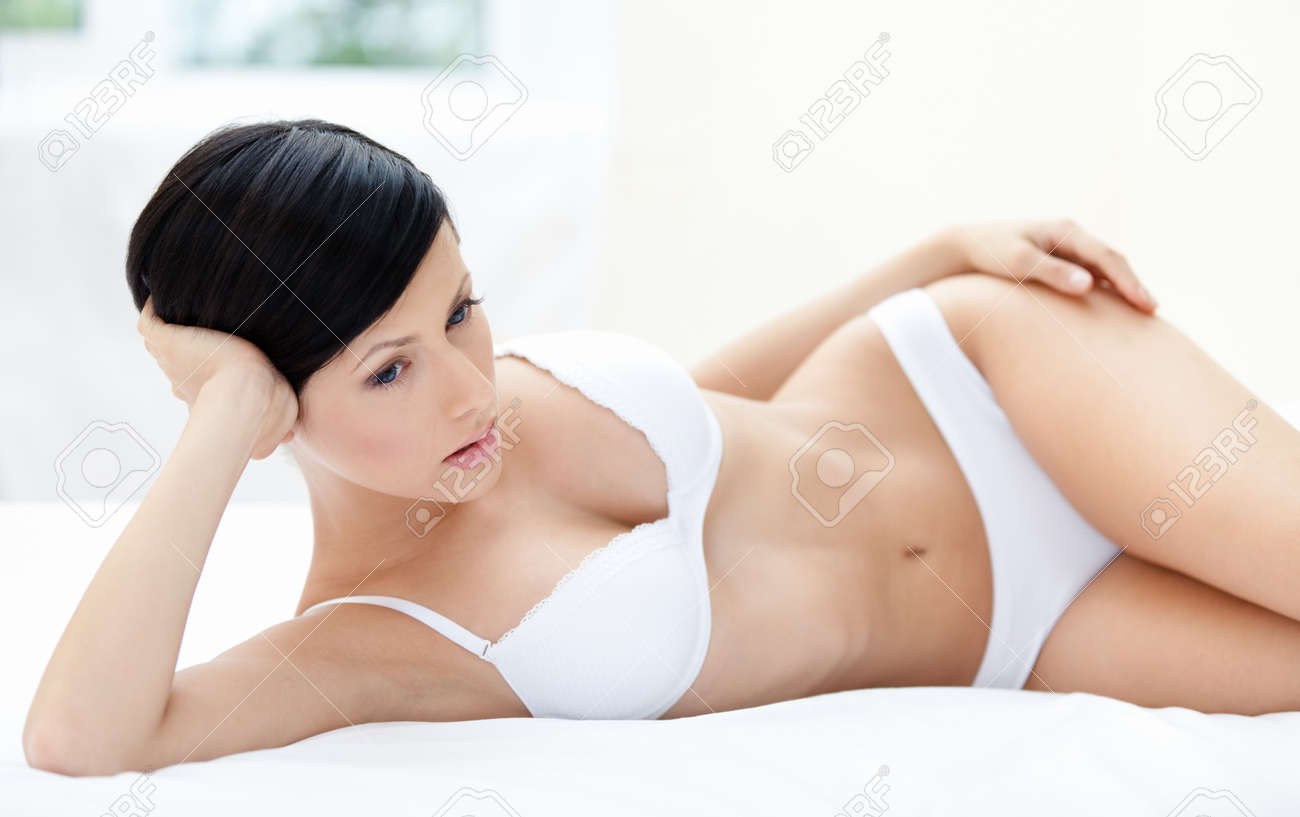 Woman in underwear is lying in the soft bed, white background Stock Photo - 15689945