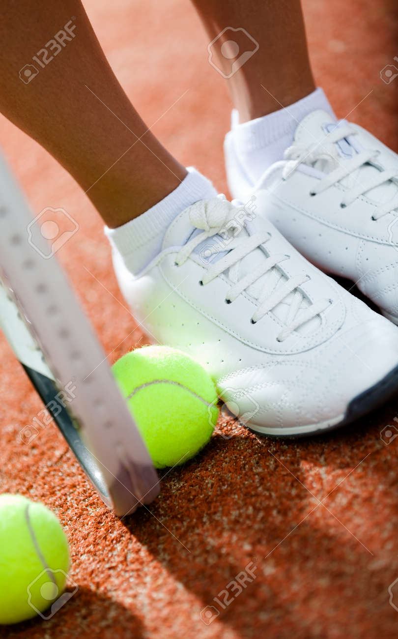 Legs of sporty girl near the tennis racket and balls Stock Photo - 15657419
