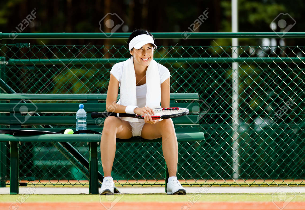 Successful female tennis player rests with bottle of water on the bench at the tennis court Stock Photo - 15868212
