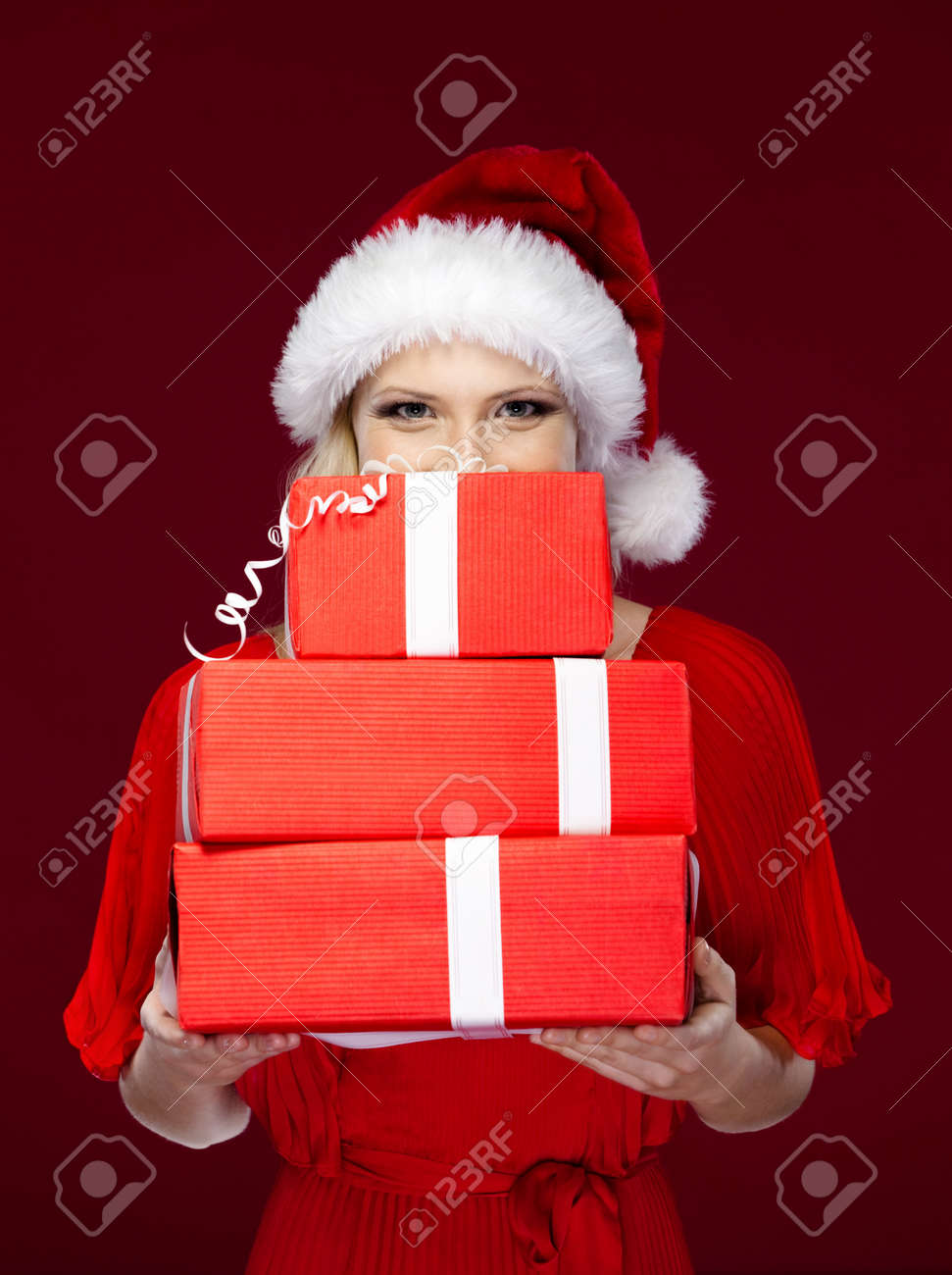Beautiful woman in Christmas cap hands a set of gifts wrapped with red paper, isolated on purple Stock Photo - 16041497