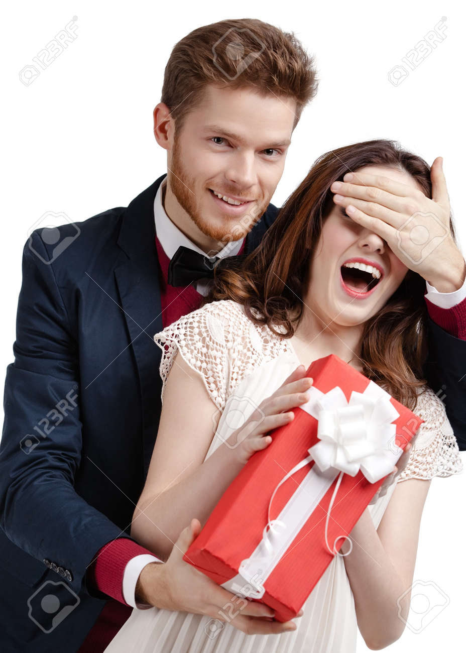 Man closes eyes of his girlfriend presenting a gift wrapped in red paper, isolated on white Stock Photo - 17457752