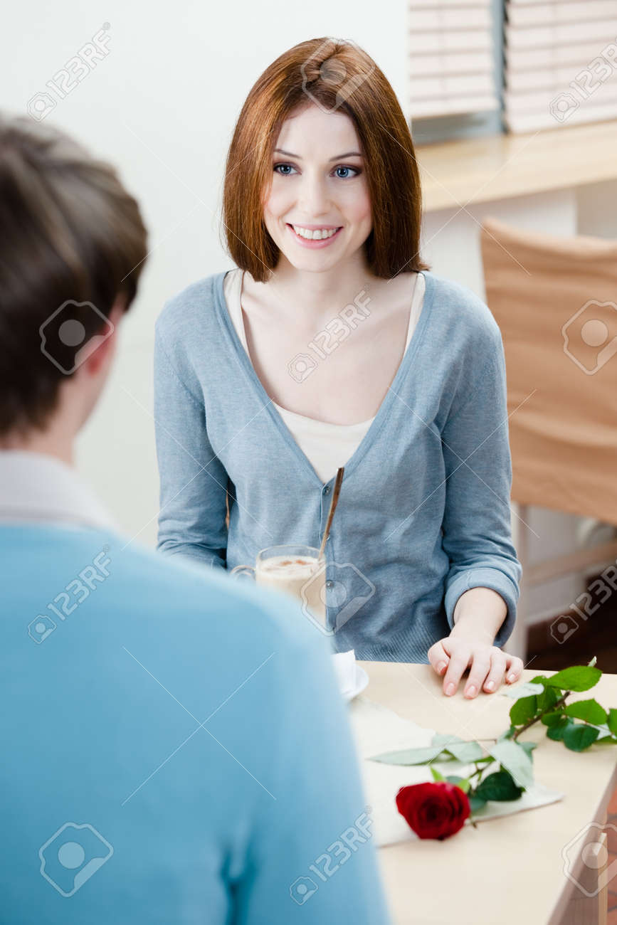 Man and woman are at the cafe table with rose near them Stock Photo - 17457796