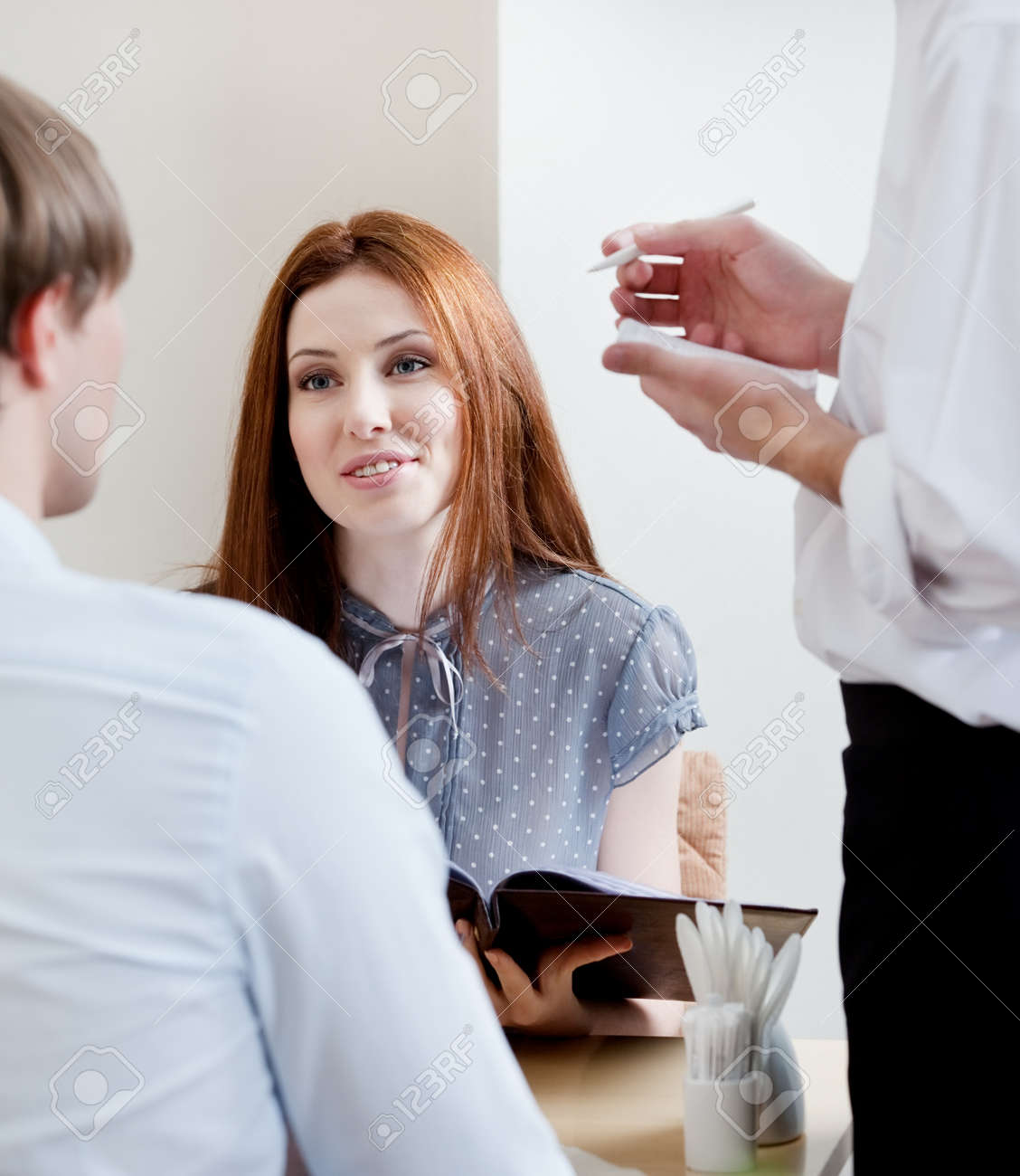 Pair makes the order to the waiter at the coffee house Stock Photo - 17457735