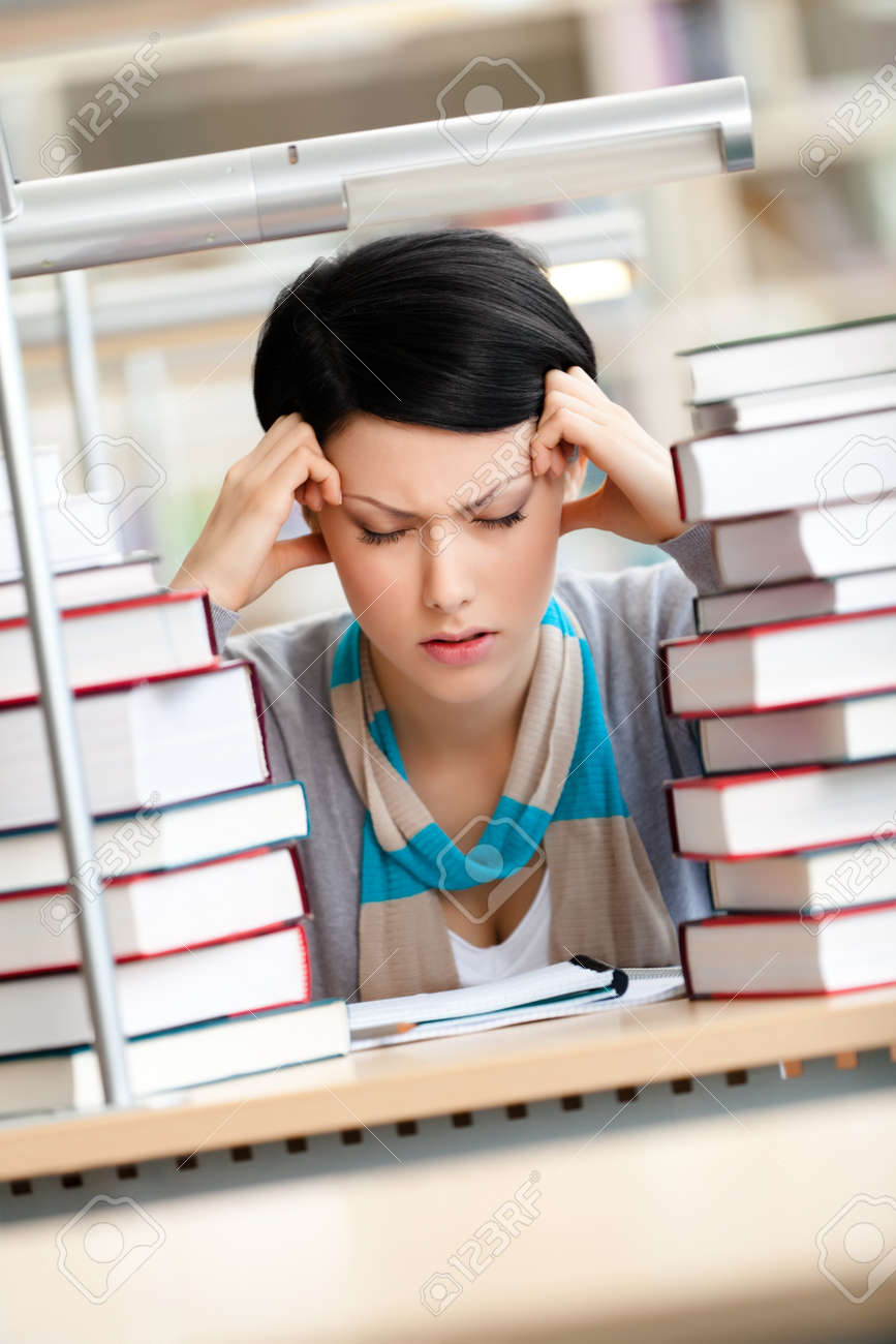 Tired young woman with headache sitting at the desk surrounded with piles of books Stock Photo - 17480589