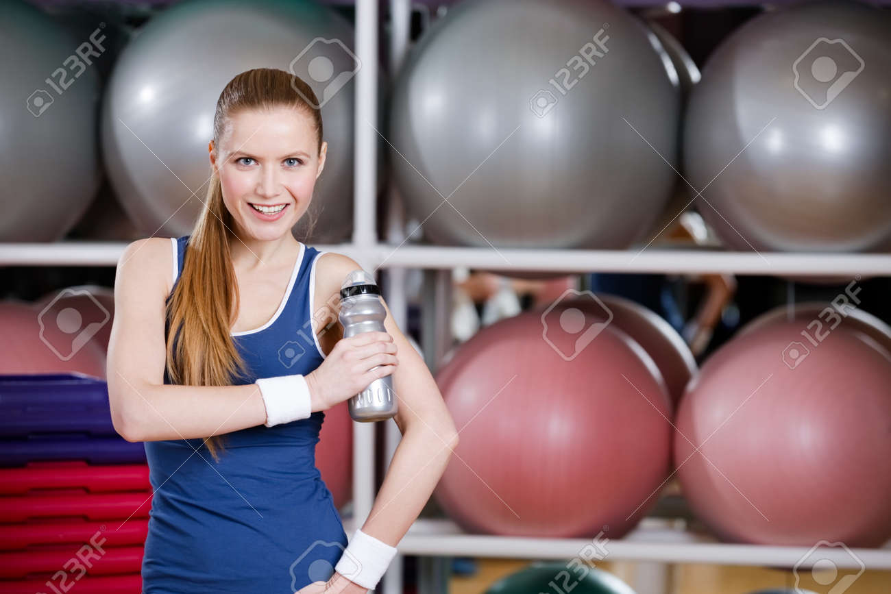 Portrait of confident young athlete woman in sportswear holding a water bottle in gym Stock Photo - 17457730