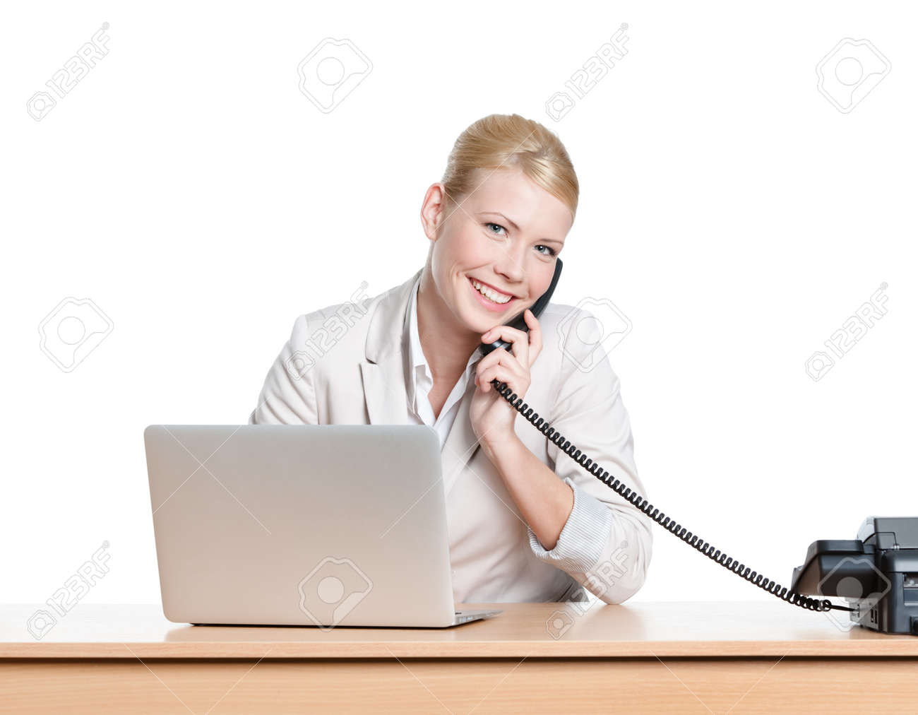Young businesswoman sitting at a office table and talking by phone, isolated Stock Photo - 17824289