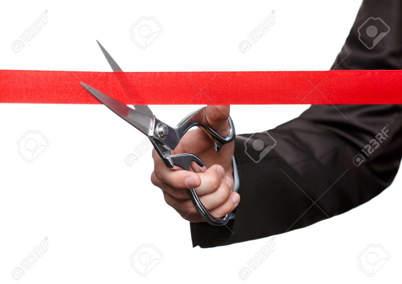 A business man cutting a scarlet ribbon with scissors, isolated on white Stock Photo - 17822391