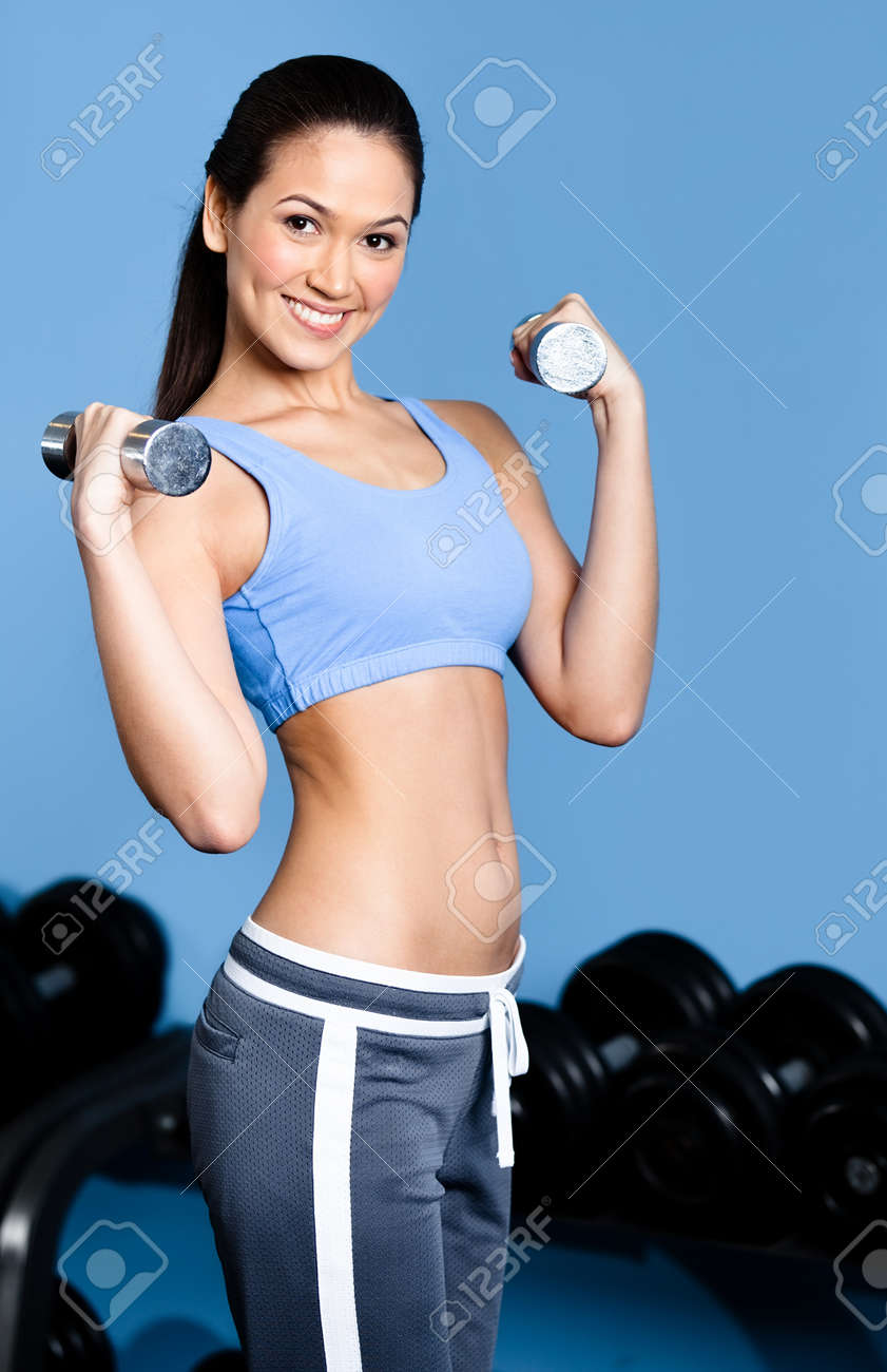 Athletic woman works out with dumbbells in gym class Stock Photo - 18076727