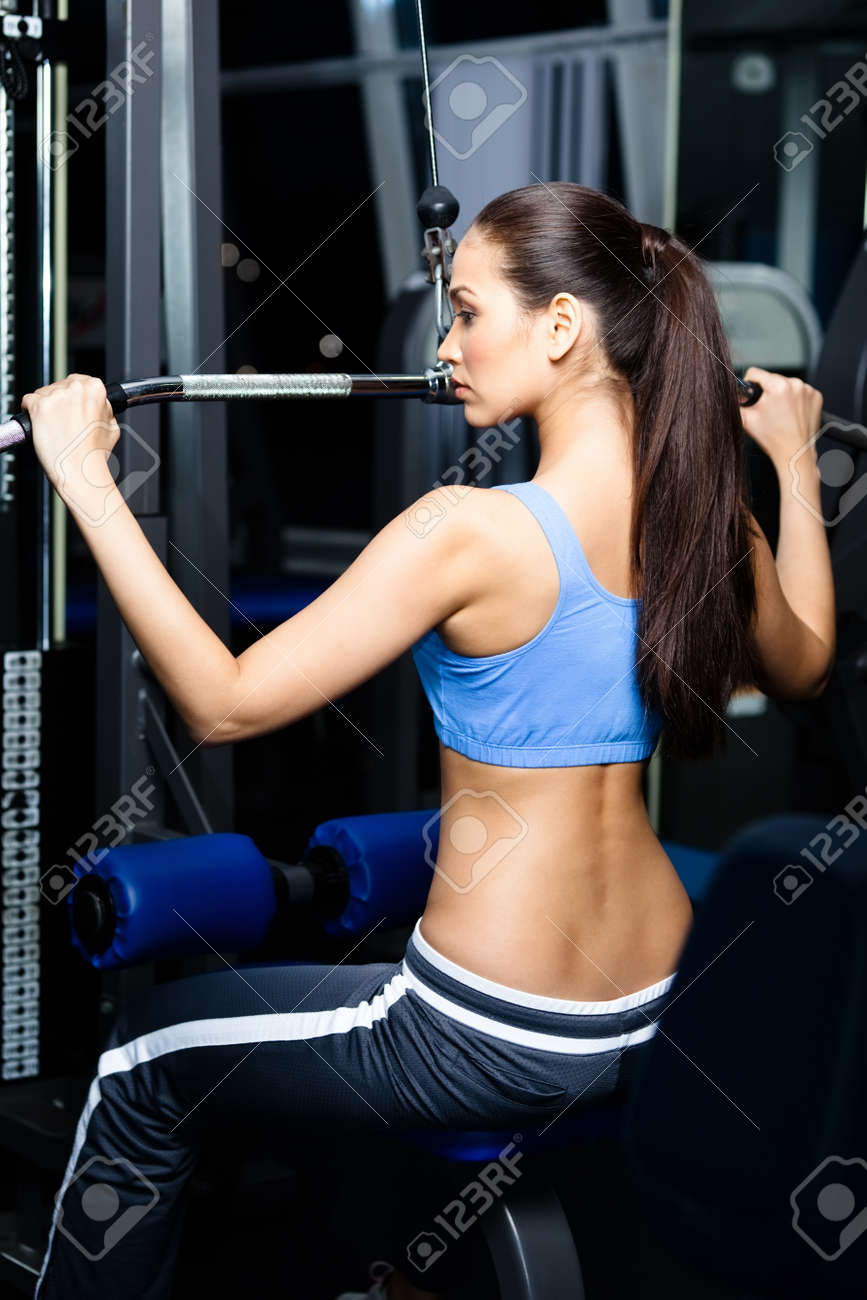 Athletic young woman works out on training apparatus in gym Stock Photo - 18077254