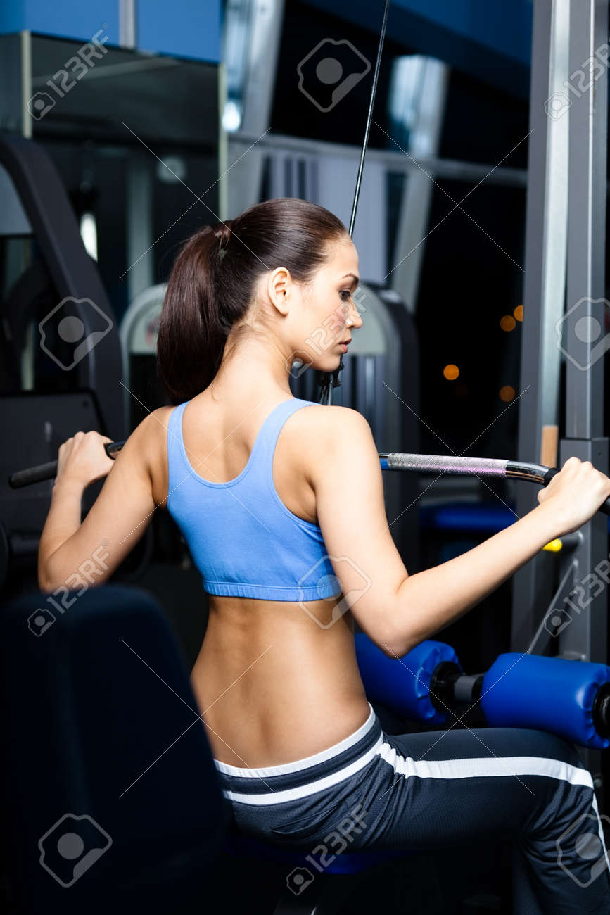 Athletic young woman works out on simulator in gym Stock Photo - 18338301