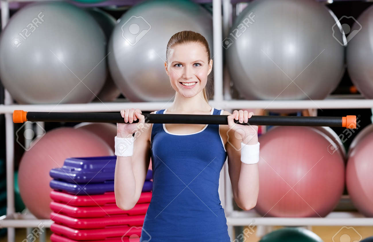 Athlete woman in sportswear working out with gymnastic stick at aerobics class Stock Photo - 19411450
