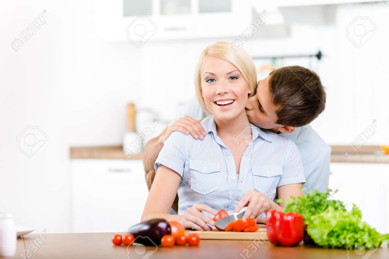 Man kisses girl while she is cooking sitting at the kitchen table full of vegetables Stock Photo - 22279302